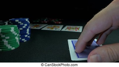 Person showing his deck at the poker game. Card player checks his hand, two aces in, chips in background on green playing table, focus on card. Hand of two aces in poker