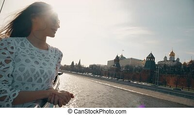 Brunette woman in white dress looking at Moscow Kremlin....
