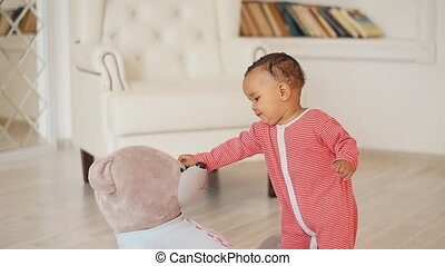 Cute smiling african baby with teddy bear toy - Cute smiling...