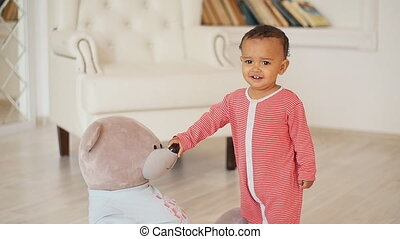Cute smiling african baby with teddy bear toy