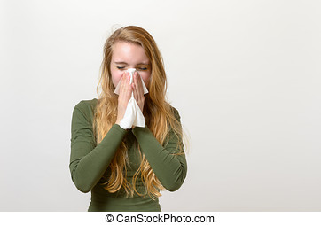 Unwell young woman blowing her nose
