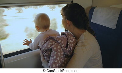 Young mother with baby in her arms traveling by train