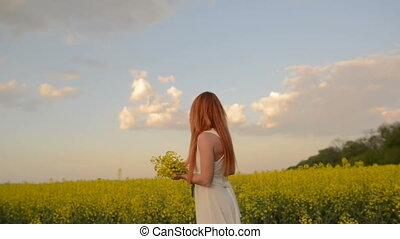 Young red-haired woman with flying hair in the midst of a flowering field