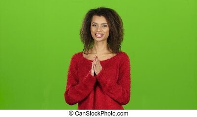Afro american woman smiles and clapping her hands, green...