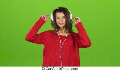 Afro american girl dancing with headphones on green screen background