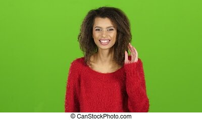 Afro american woman in red sweater contagiously laughs,...