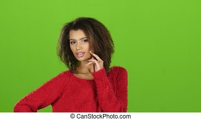 Afro american girl posing on camera, green screen. Close ups...