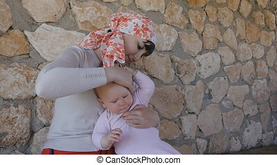 Young mother putting sunblock cream on her baby