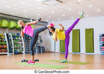 Two athletic women working out in gym, doing sidekicks...