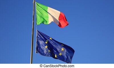 Flags of Italy and Europe waving in the blue sky background....