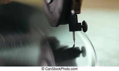 Vintage old gramophone plays a vinyl record - close up,...
