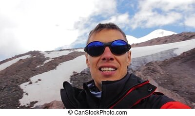A man makes selfie against the background of a mountain in...