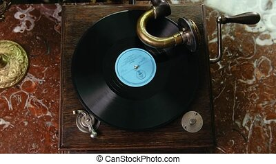 Vinyl record spinning on vintage old gramophone - top view,...