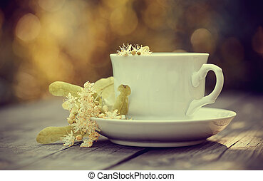 Tea with flowers of a linden in a white cup