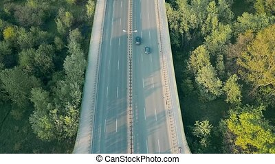 Aerial shot of a highway across the forest in the evening....