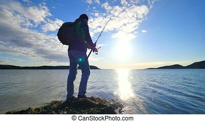 The fisherman with green sporty backpack is checking fishing...