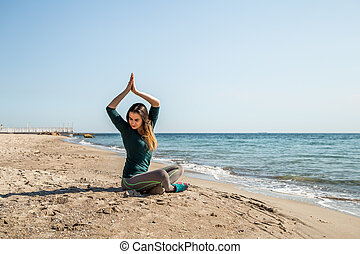 Girl in sportswear fitness by the sea listening to...