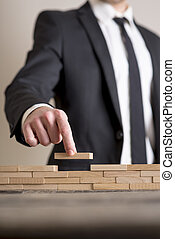 Businessman in business suit placing wooden blocks on table