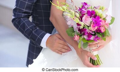 The bridegroom embraces the bride with flowers.