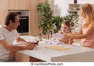 Delighted father enjoying holiday with family indoors -...