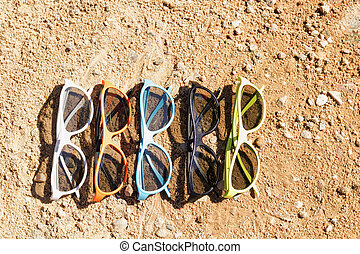 Set of sunglasses on the sand. Concept for sumer, vacation...