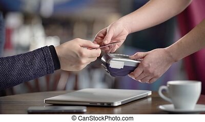Close up of male and female hands doing process of cashless payment in restaurant. Waitress giving to customer POS-terminal and cash voucher after the pay. Man making money transfer with plastic card.