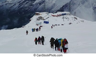 A group of people descends from Mount Elbrus to the base...