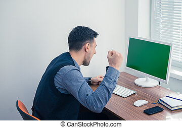 Furious young businessman ready to smash his computer....