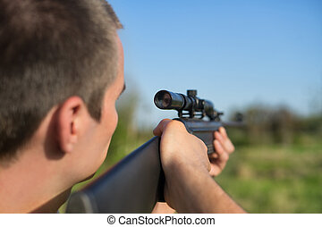 The man takes aim at the target with a sniper rifle....