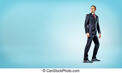 A businessman standing on blue background in half turn and...