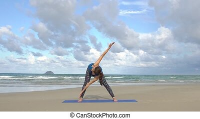Young woman training on the beach in front of sea. Morning gymnastic exercises. Healthy active lifestyle concept.