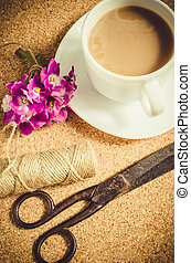 Flowers, scissors and jute next to cup of coffee.