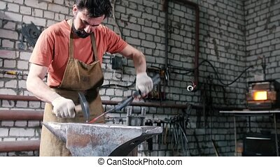 Muscular blacksmith in forge hammering steel products, small...