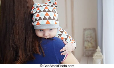 Newborn baby boy in mother's arms - Newborn baby boy asleep...