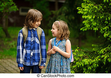 Two little school students cheerfully communicate on the...