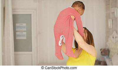 Mother playing with her child. Mom holds boy in her arms