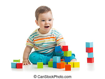 Baby building from toy blocks. Isolated on white background