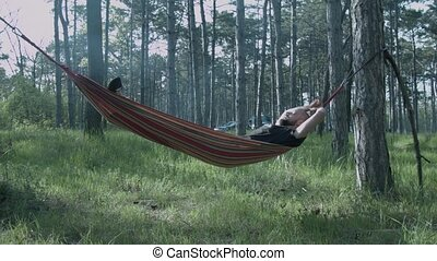 A young man is sleeping on a hammock in the forest. The tourist is resting on a hammock.