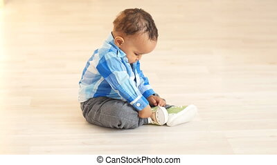 Cute african baby sitting on a floor - Adorable african baby...