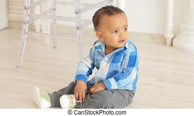 Cute african baby sitting on a floor