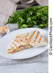shawarma in thin pita bread with chicken and vegetables on a...