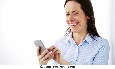 happy businesswoman with smartphone at office - business,...