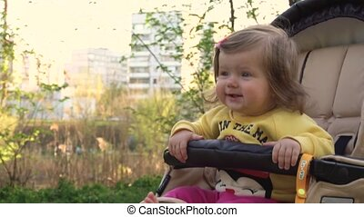 Baby girl in carriage - Baby girl sitting in carriage in...