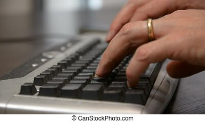 Hands of a man working at computer typing on keywords on...