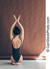Back view of beautiful dancer posing on studio background -...