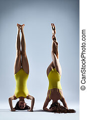 Two young women doing yoga asana supported headstand....