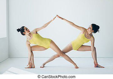 Two beautiful women doing yoga asana extended side angle...
