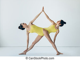 Two beautiful women doing yoga asana extended triangle pose...