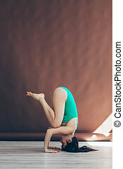 Young woman doing yoga asana supported headstand. side view