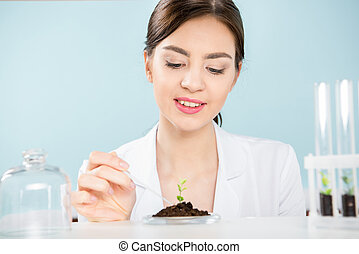 Female scientist with green plant